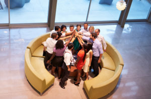 Businesspeople Giving Each Other High Five In Office Lobby